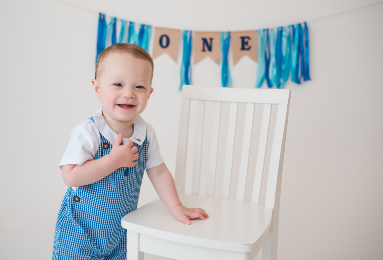 smiling one year old boy with hand on chair, birthday banner in background