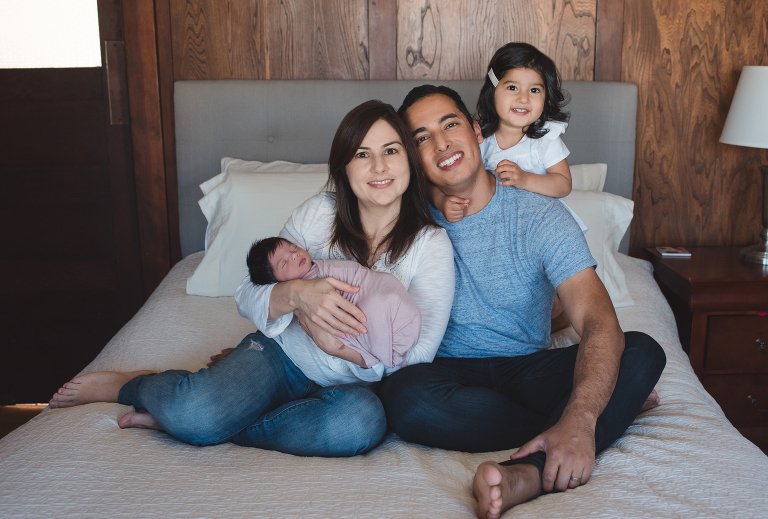 mom, dad, and big sister looking at camera, newborn baby girl