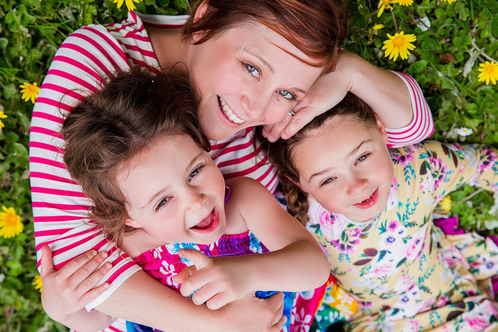 colorful portrait of Emily Vaccaro of Photography by Emily Payne with her two young girls, field of yellow flowers beneath them