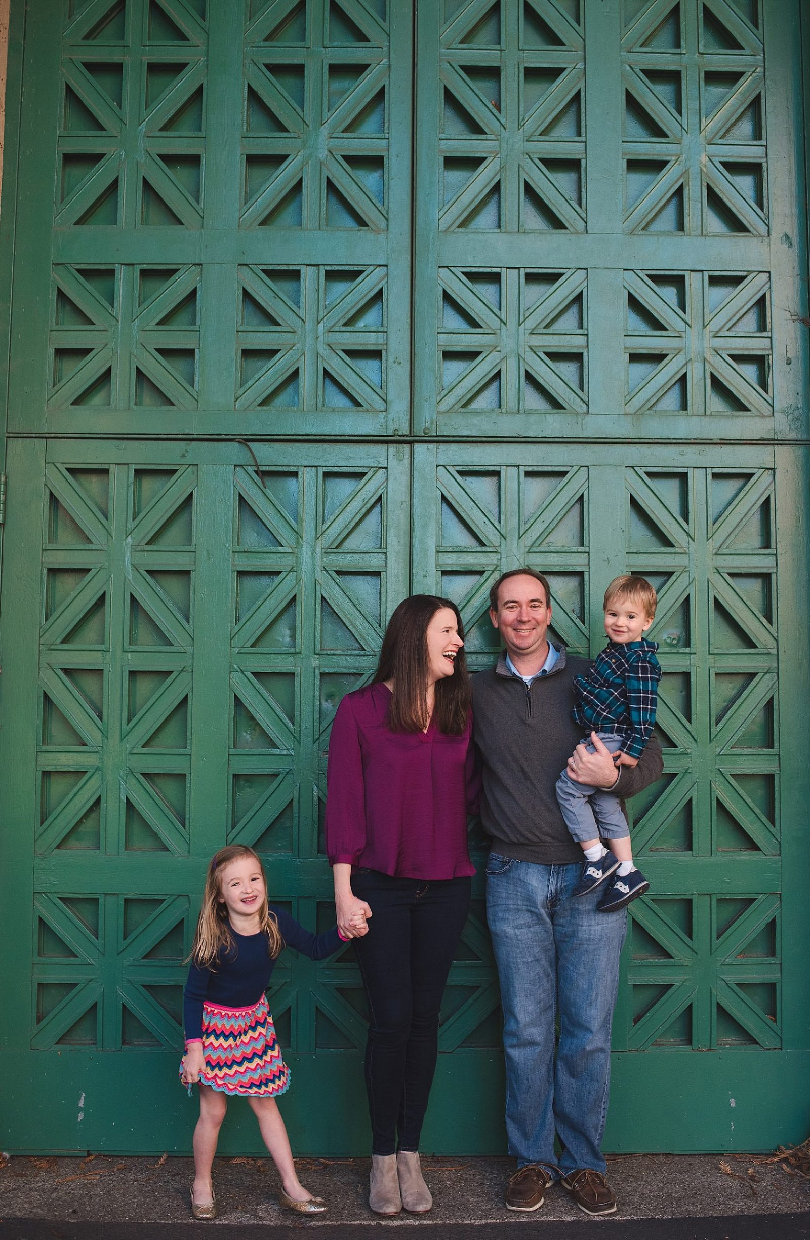 family of four in front of a backdrop of ornate green doors in San Francisco