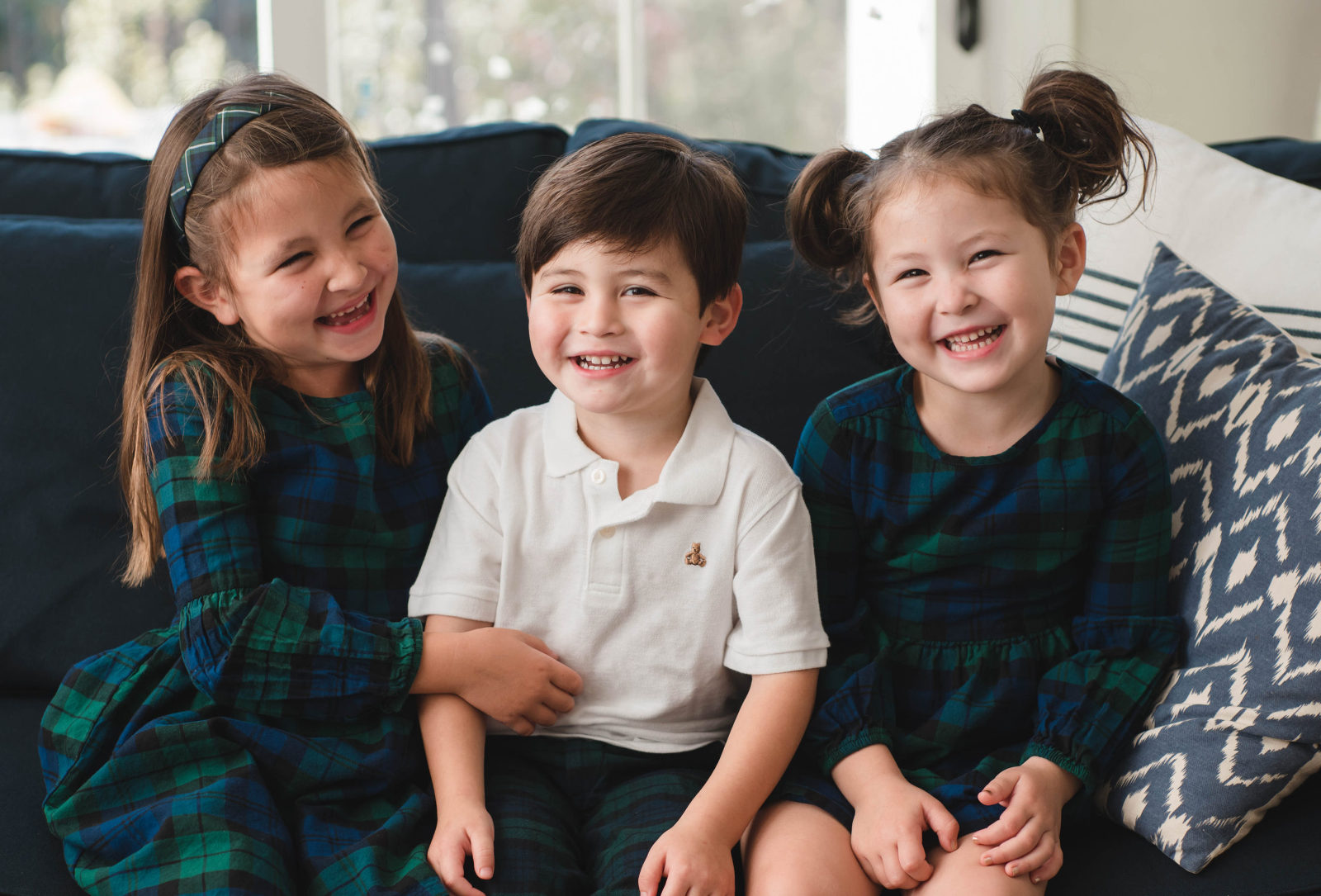 cute holiday sibling portrait, girls in black watch plaid dresses, brother in a polo and plaid pants, dark blue couch, blue ikat pillow