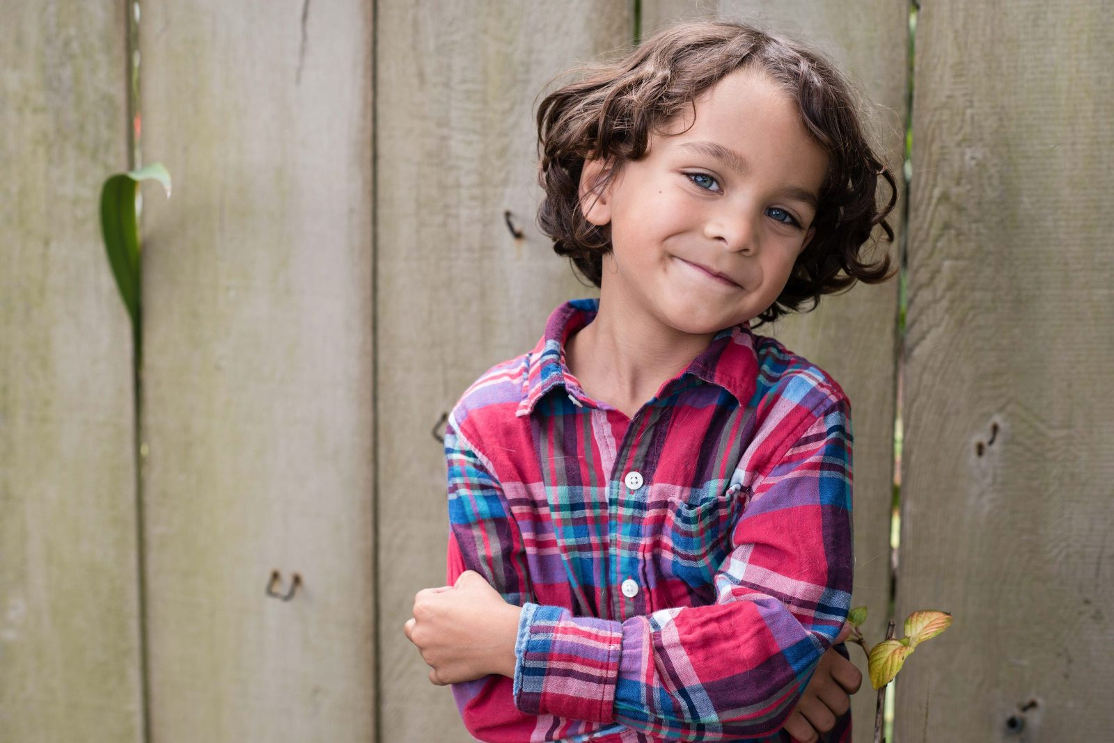 proud young child with blue eyes and brown curly hair wearing a plaid shirt, rustic fence background