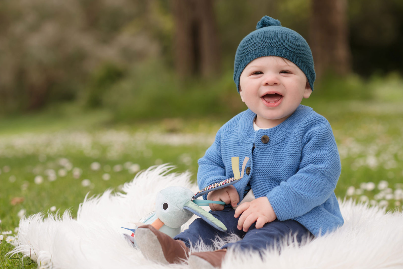 happy sitting baby boy with dark teal knit cap, powder blue knit sweater, multi-fabric toy rabbit, sitting on a white flokati in a green field